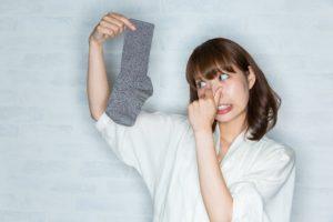 臭い靴下を持つ女性